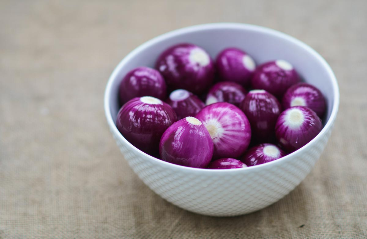 A bowl full of red onions, grown organically